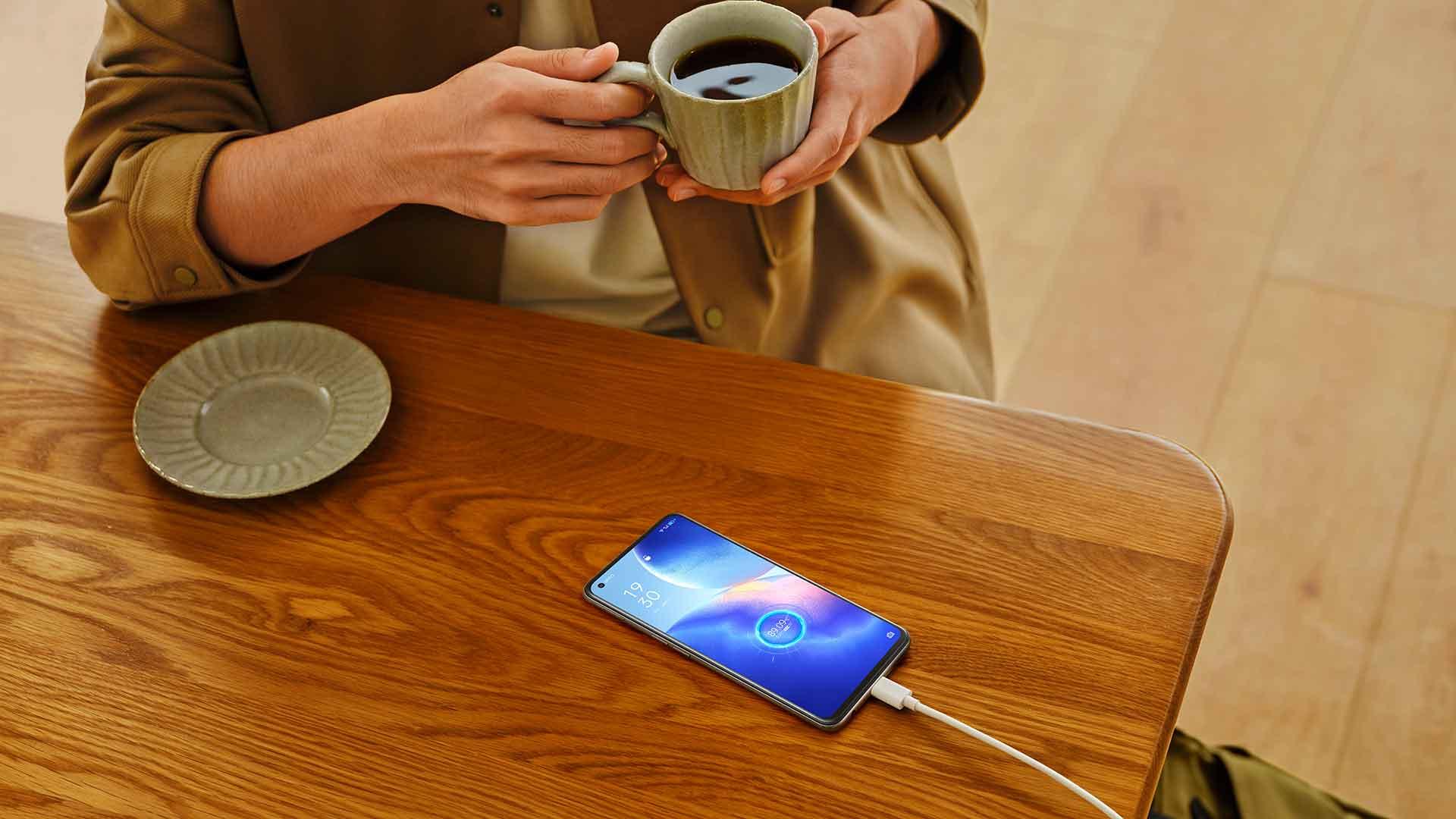 Eine Frau lädt ihr Oppo Find X3 Lite 5G am Kabel und trinkt dazu Kaffee.