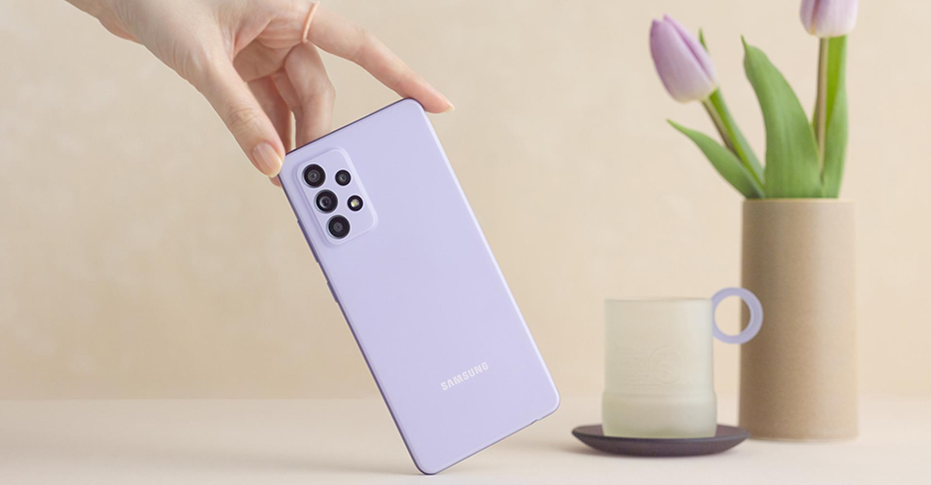 Hand hält das Galaxy A52 vor Blumenvase