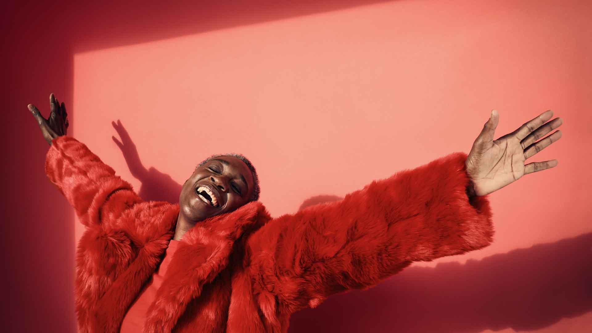 Eine Frau mit rotem Fake-Fur-Mantel streckt lachend die Arme aus.