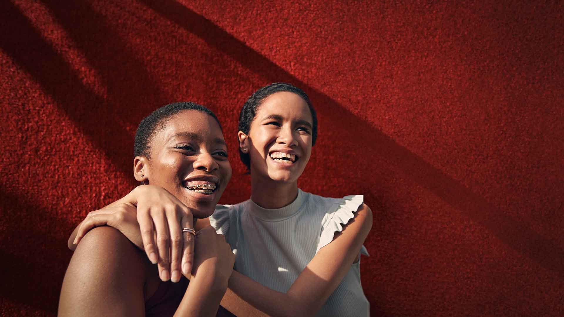 Zwei Mädchen stehen lachend vor einer roten Wand, die rechte umarmt die linke.