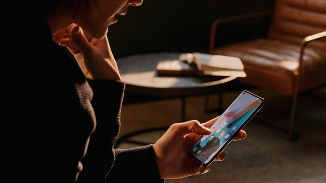 FRau hält Oppo Find X3 Pro vor Ledersessel
