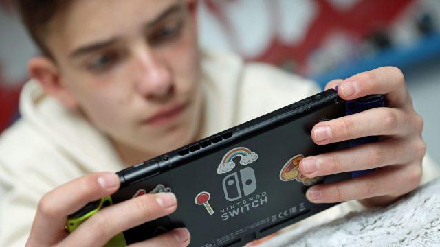 Junger Mann zockt Spiel an der Nintendo Switch.
