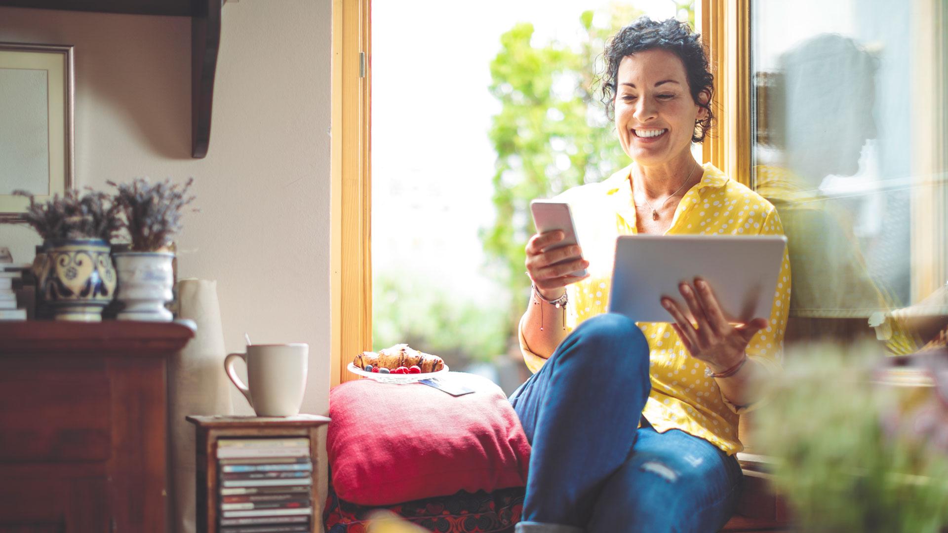 Eine Frau sitzt an einem Fenster und hält ihr Smartphone in der Hand