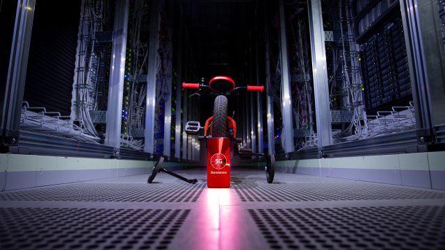 """Ein rotes Fahrrad mit Stützrädern, davor ein Smartphone, das """"5G Standalone"""" auf dem Display zeigt."""