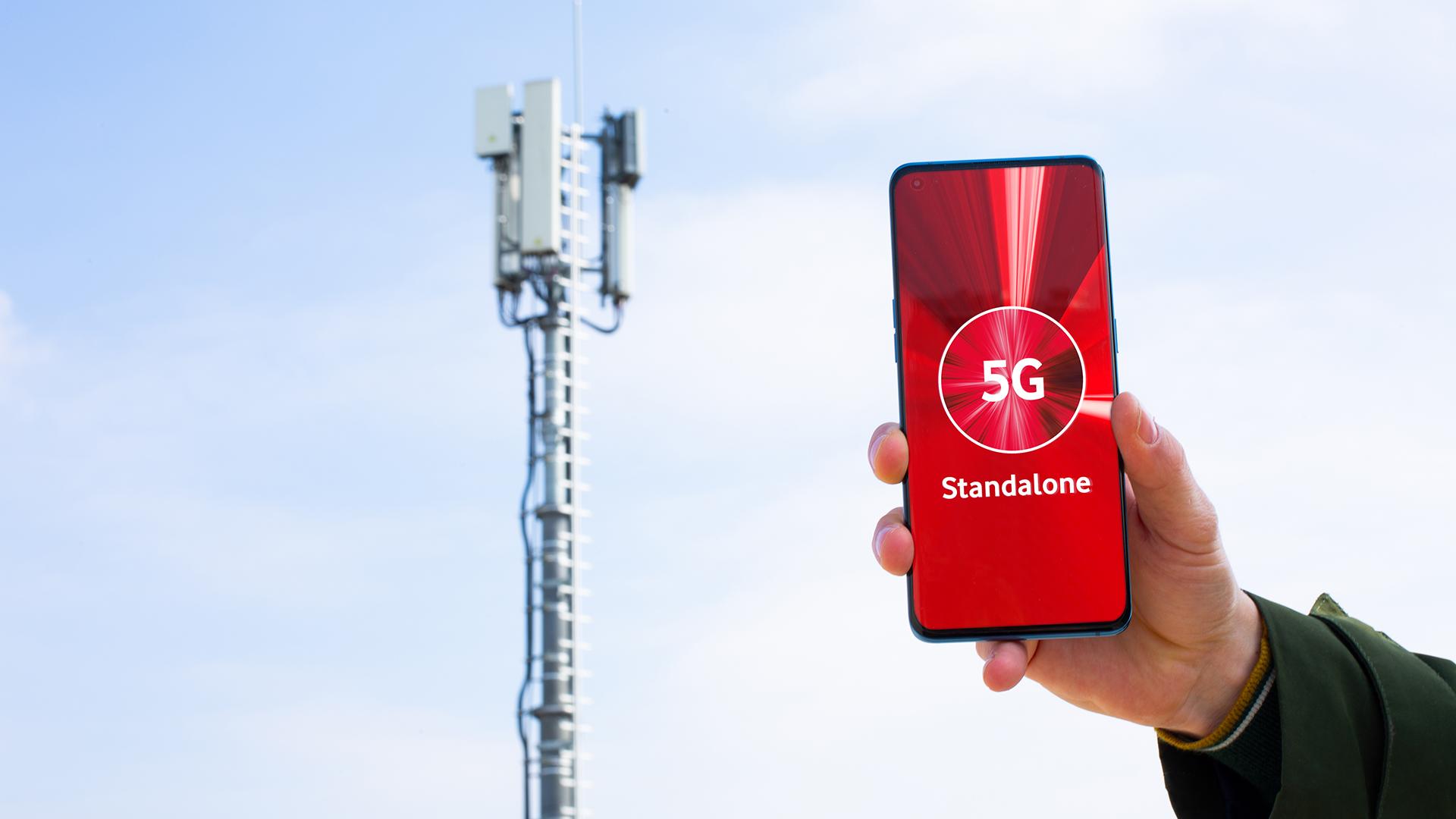 """Ein Smartphone, das """"5G Standalone"""" zeigt, dahinter ein Mobilfunkmast."""