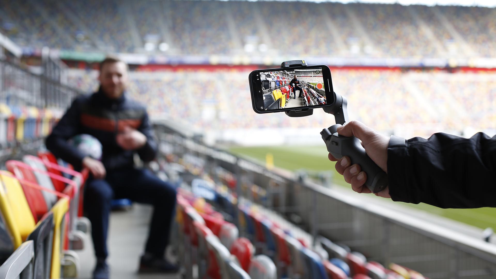 Ein Smartphone überträgt eine Liveaufzeichnung aus dem Fußball-Stadion.