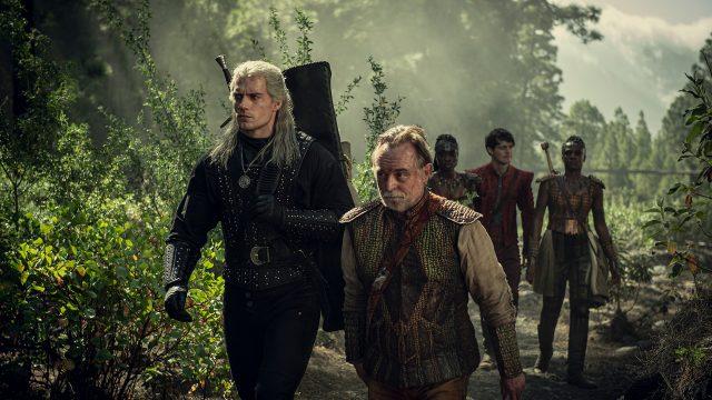 Hexer Geralt (Henry Cavill) streift mit Barde Rittersporn (Joey Batey) durch einen Wald.