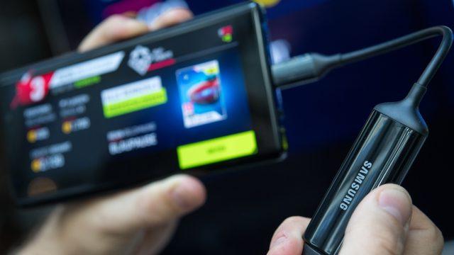Hand hält Samsung Galaxy Note 9 und Kabel vor Bildschirm