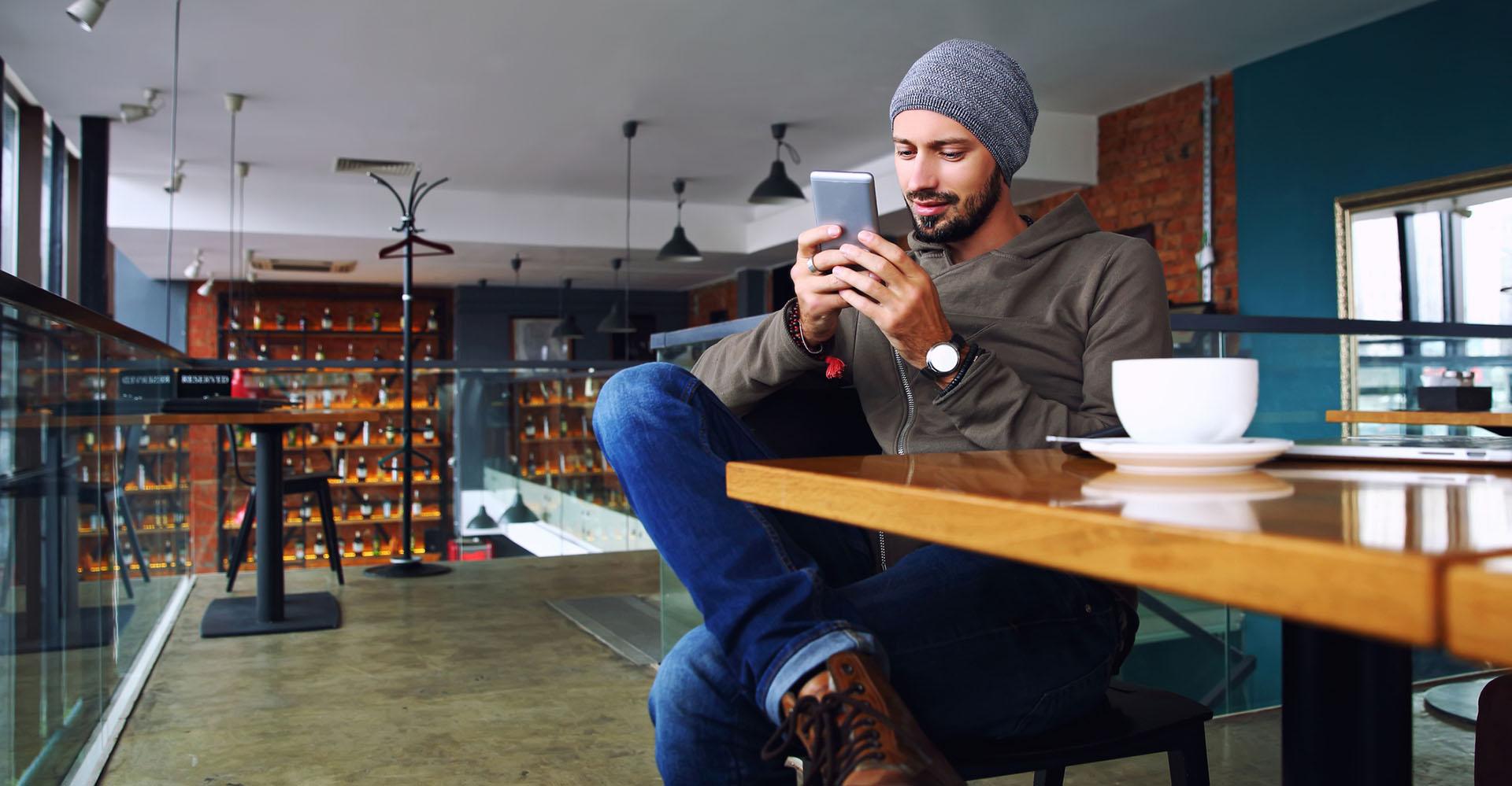 Mann nutzt Smartphone im Café