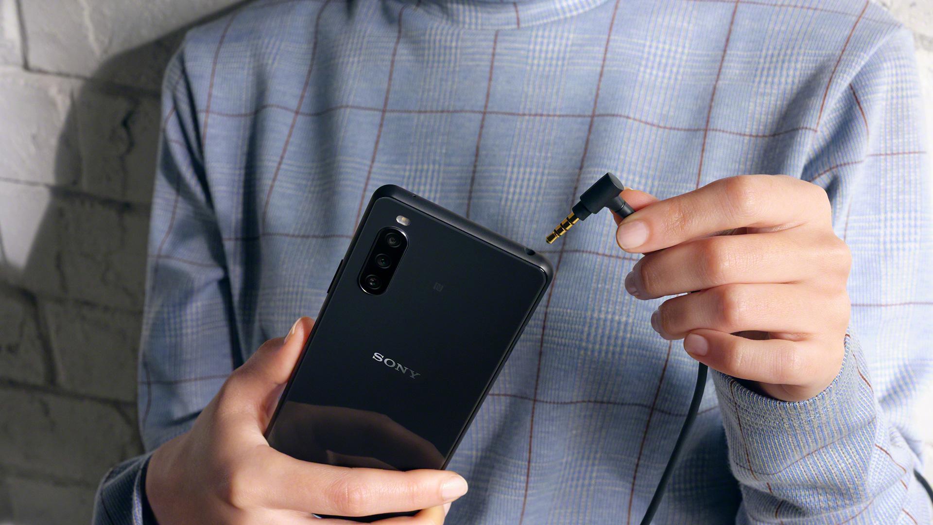 Eine Frau schließt Kopfhörer an das Sony Xperia 10 III 5G an.