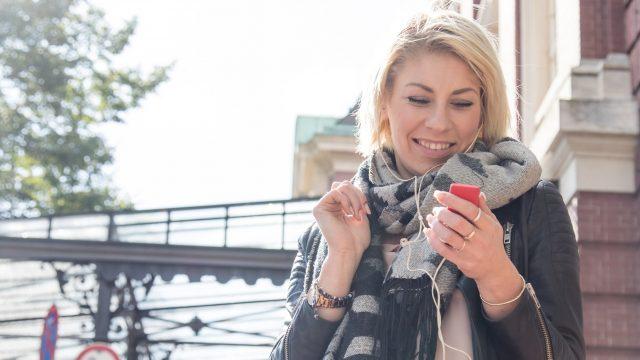 Frau guckt draußen auf iPod touch und lacht