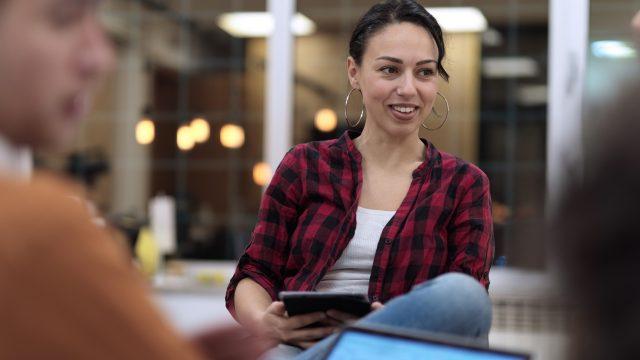 Frau hält Tablet in einem Meeting