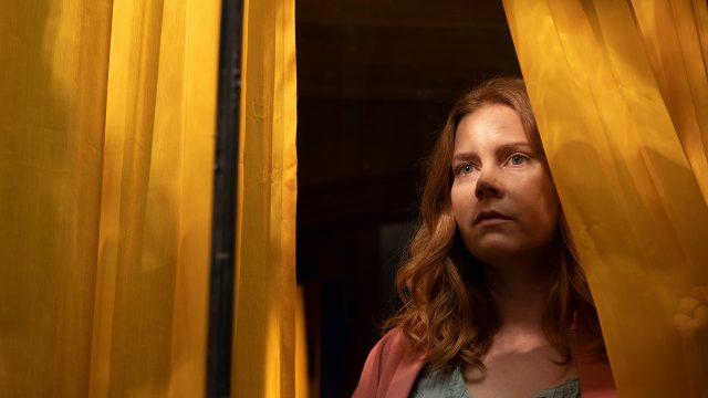 """Anna Fox (Amy Adams) sieht aus einem Fenster mit gelben Vorhängen im Film """"The Woman in the Window""""."""