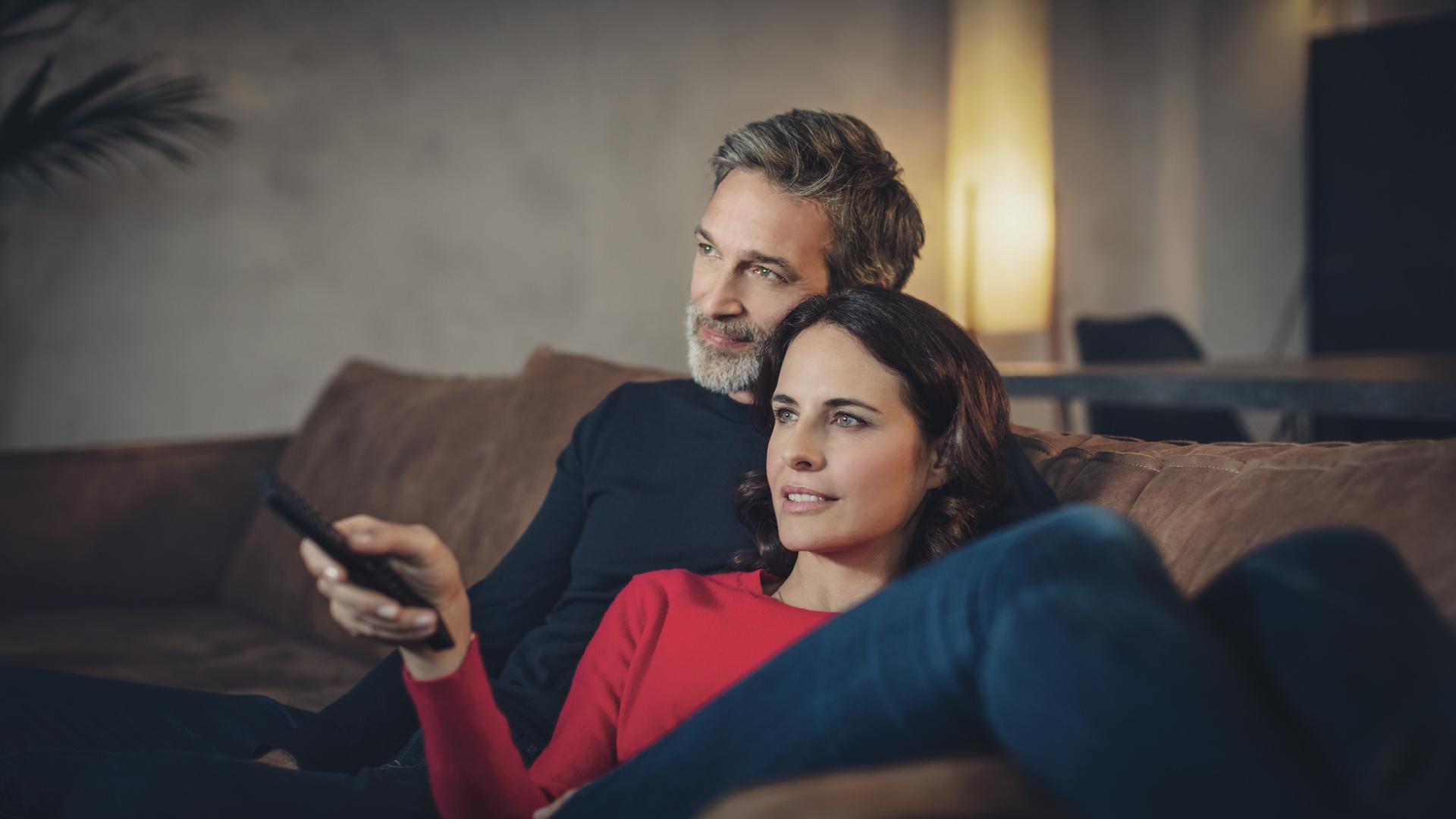 Ein Paar sitzt gemeinsam auf der Couch und sieht fern, die Frau schaltet dabei mit der Fernbedienung um.