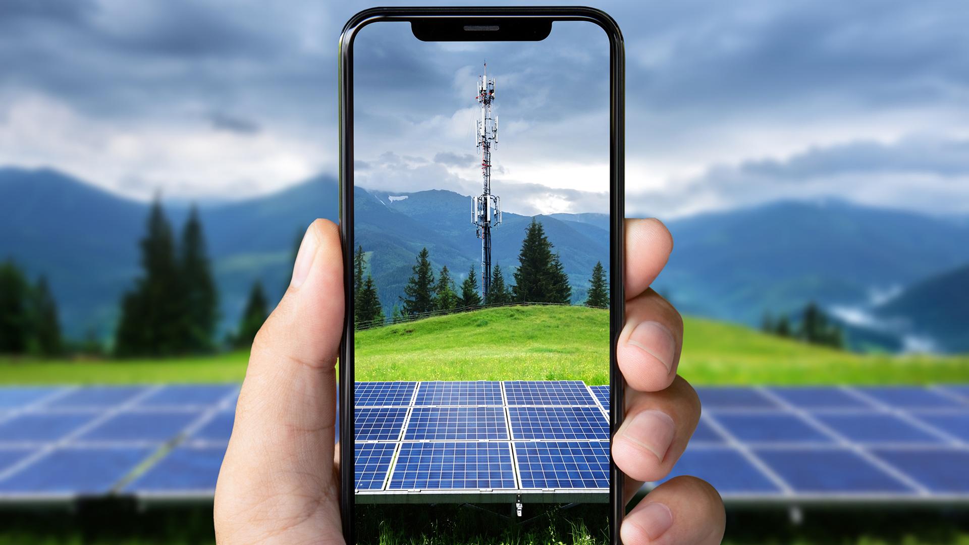 Auf dem Display eines Smartphones ist eine Solarzelle zu sehen, im Hintergrund eine Berglandschaft mit einem Mobilfunkmast.