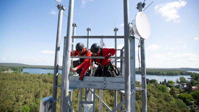 Vodafone-Techniker:innen montieren 5G-Antennen auf einer Mobilfunk-Station in Berlin.