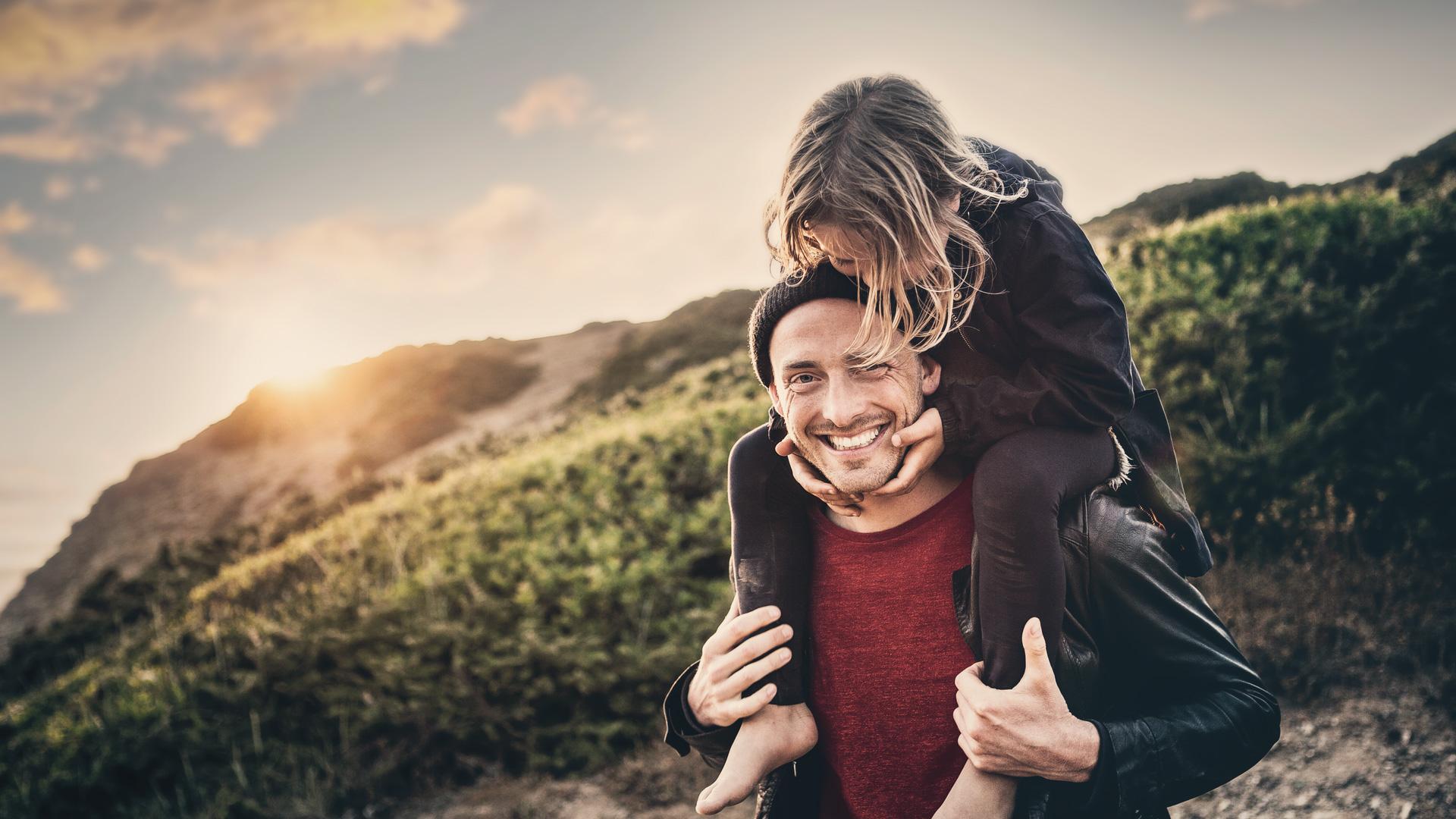 Ein Vater trägt seine kleine Tochter auf den Schultern, im Hintergrund sieht man einen begrünten Hang.