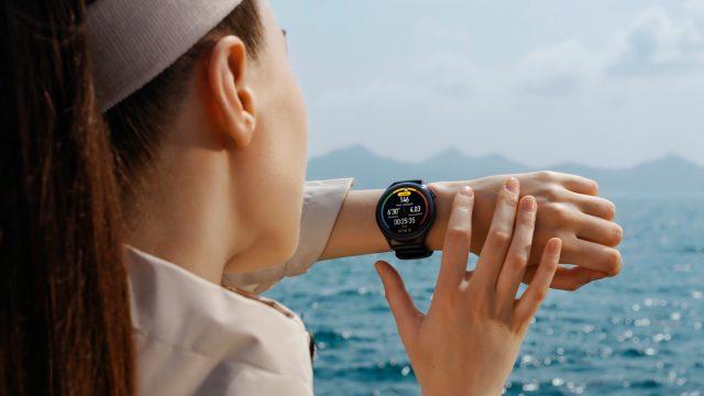 Frau am Strand guckt auf Huawei Watch 3 in Schwarz