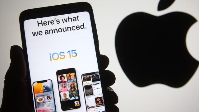 Hand hält iPhone mit iOS 15 vor Apple-Logo