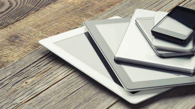 Verschiedene Tablets auf einem Holztisch