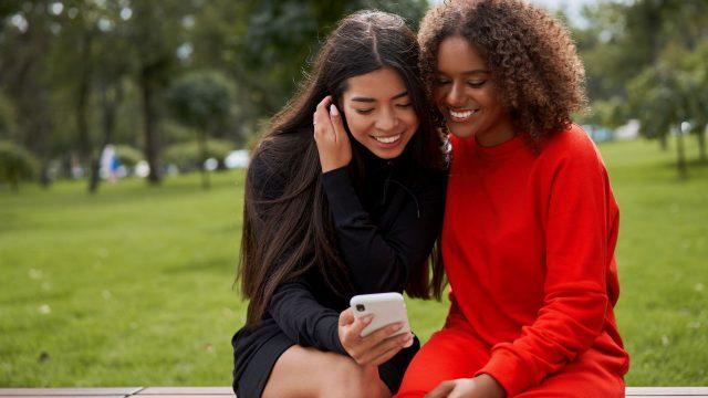 Zwei Frauen schauen auf ein Smartphone.
