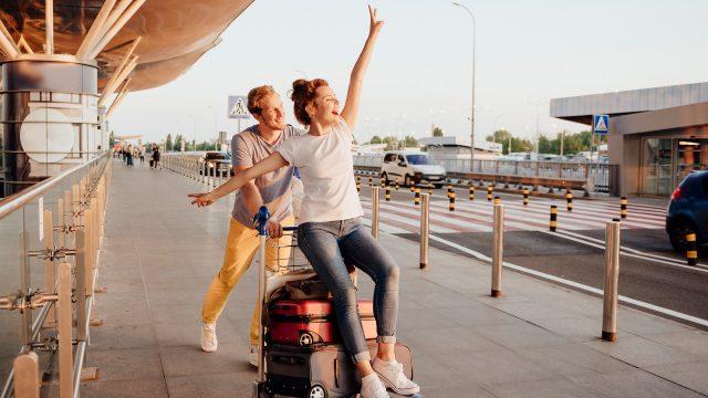 Ein Mann schiebt Koffer und seine Partnerin auf einem Gepäckwagen vor dem Flughafen an der Straße entlang.