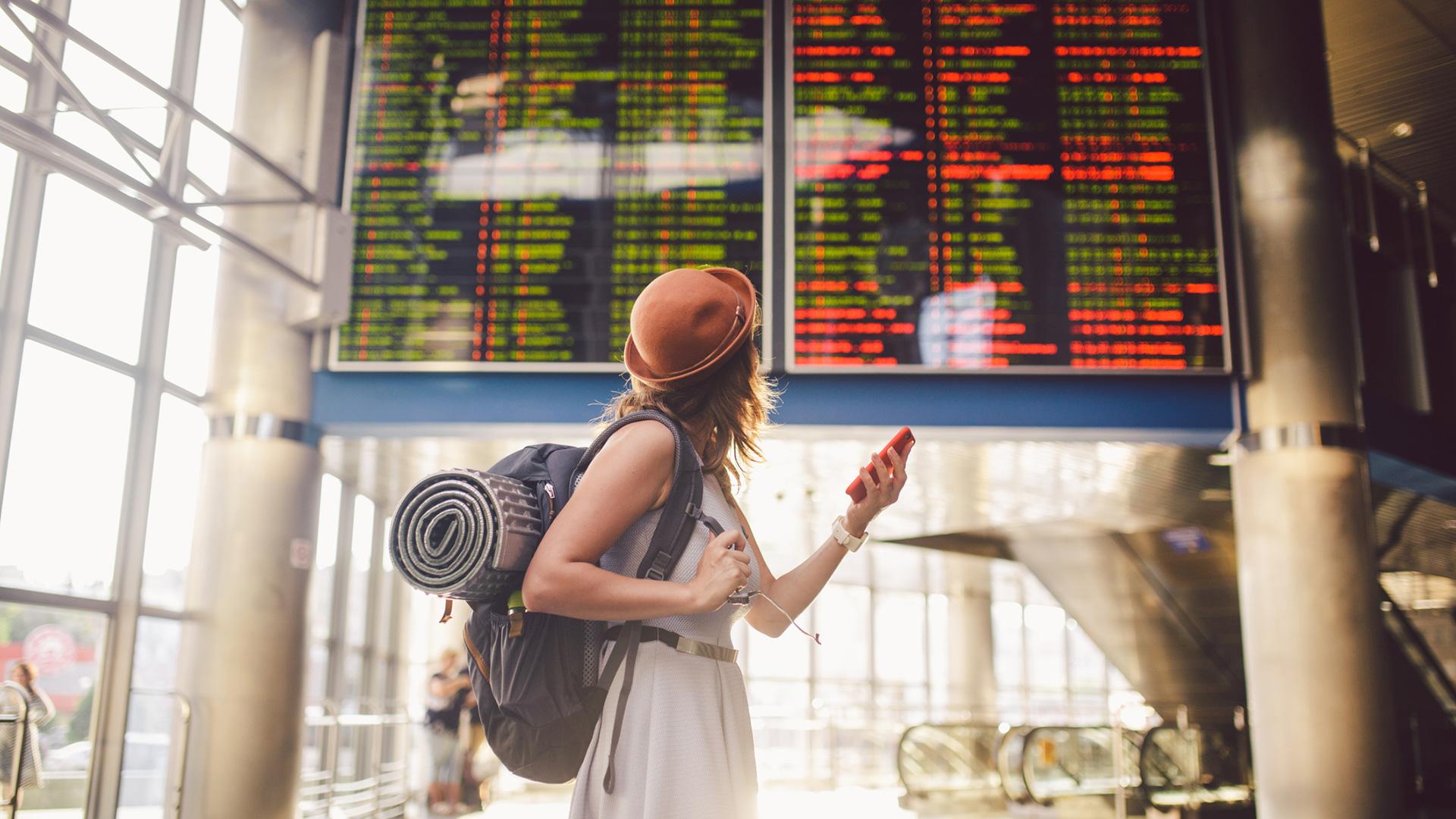 Eine Frau mit Hut und Rucksack prüft die Anzeigetafel am Flughafen und hält ihr Smartphone in der Hand.