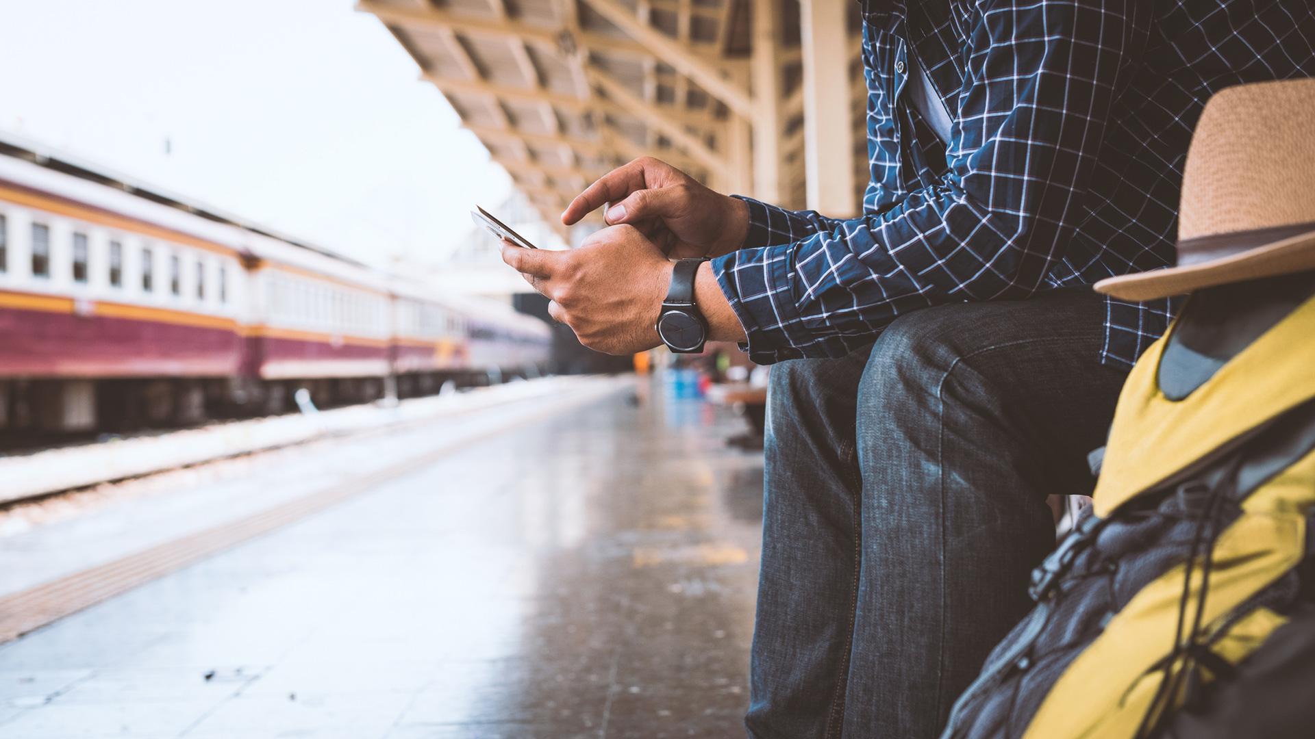 Ein Mann sitzt mit seinem Gepäck am Bahnhof und tippt etwas in sein Smartphone.