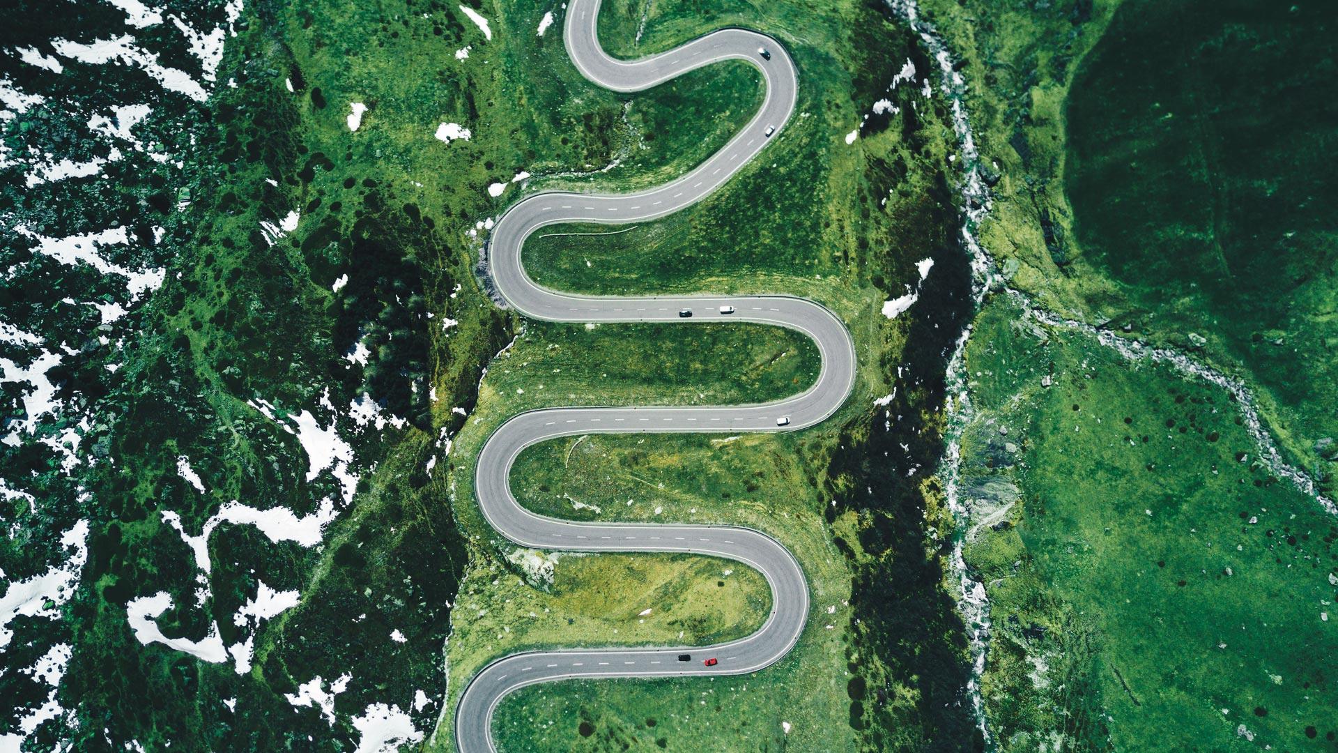 Eine Luftnahme zeigt, wie Autos auf einer Bergstraße entlang fahren.