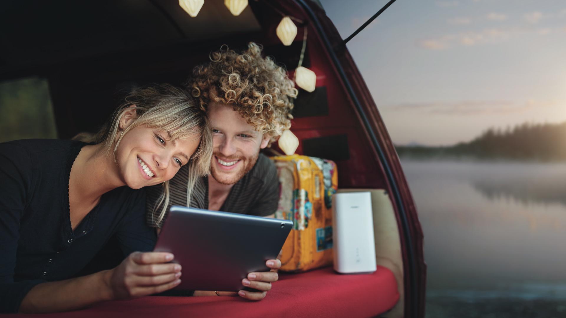 Ein Paar liegt im Kofferraum seines Campers und schaut sich etwas auf dem Tablet an.