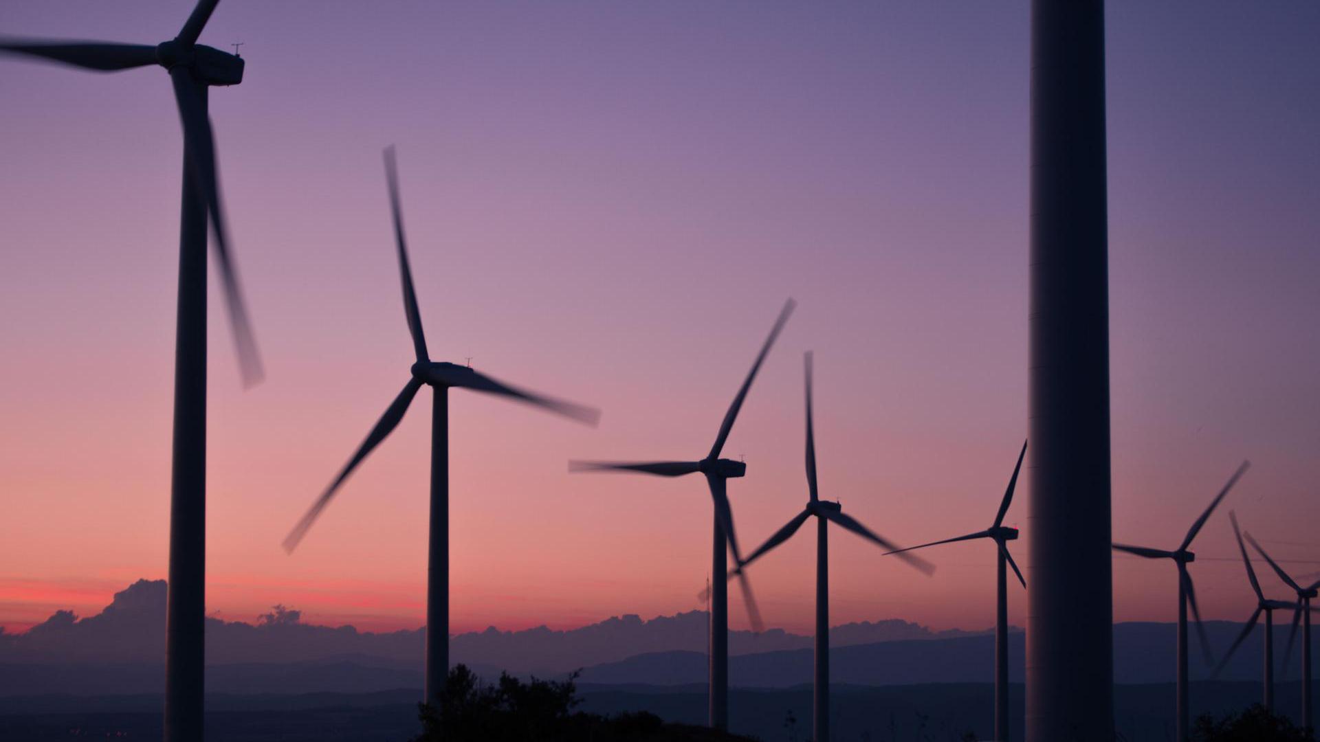 Mehrere Windräder drehen sich im Sonnenuntergang.