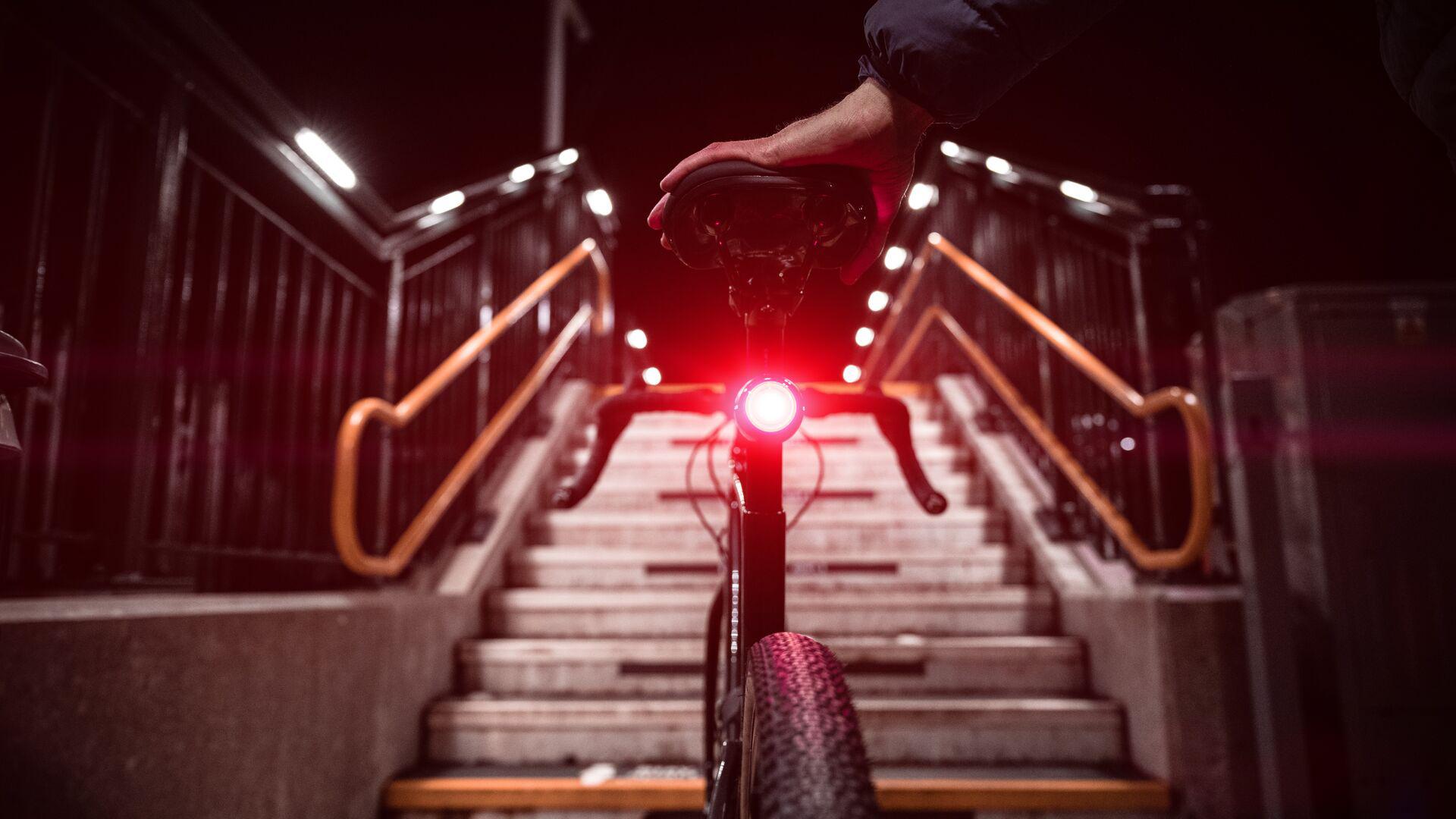 Ein Fahrrad steht vor einer Treppe, am Rad angebracht ist das smarte Vodafone Curve Bike Rücklicht.