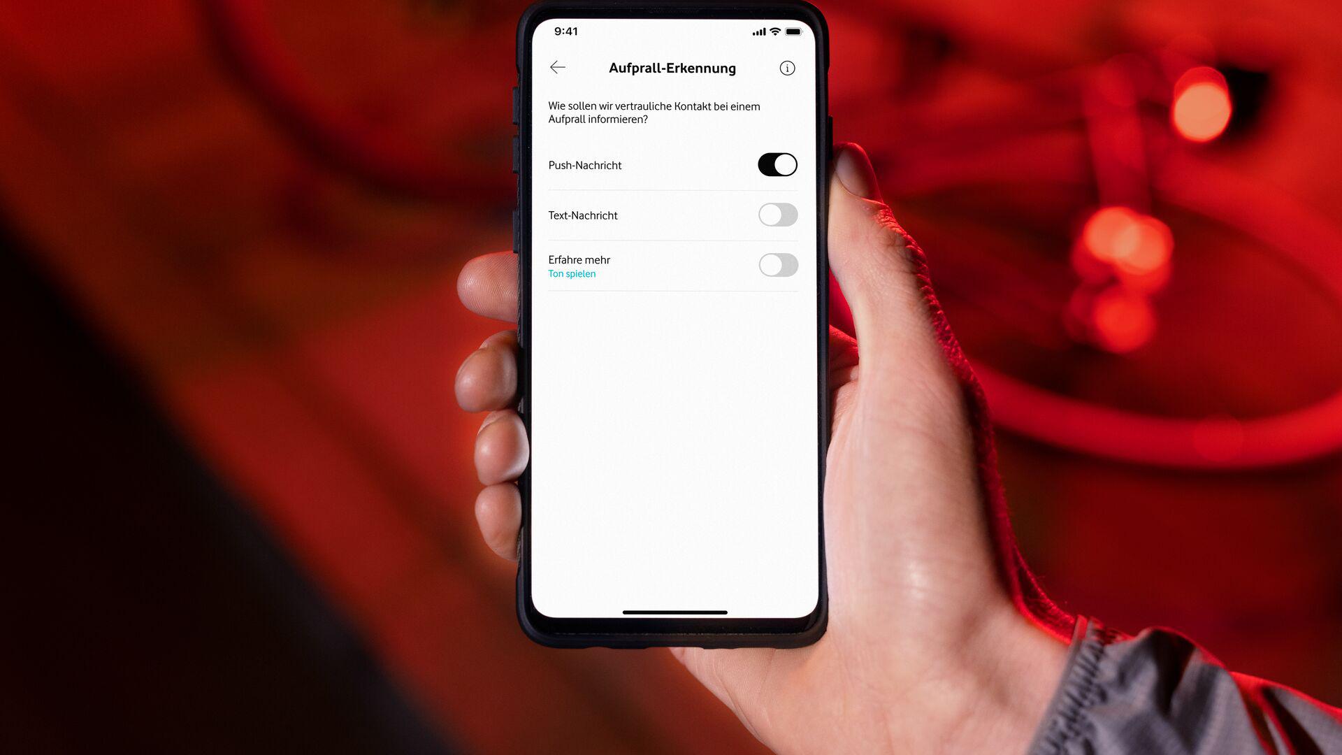 Eine Hand hält ein Handy, über das die Vodafone Smart App aufgerufen ist. Für das Vodafone Curve Bike können Kontakte festgelegt werden, die bei einem Sturz mit dem Rad alarmiert werden.