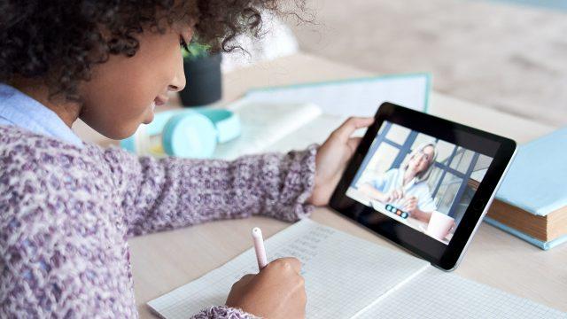 Ein Mädchen bearbeitet Schulaufgaben mithilfe einer Betreuerin über das Tablet.