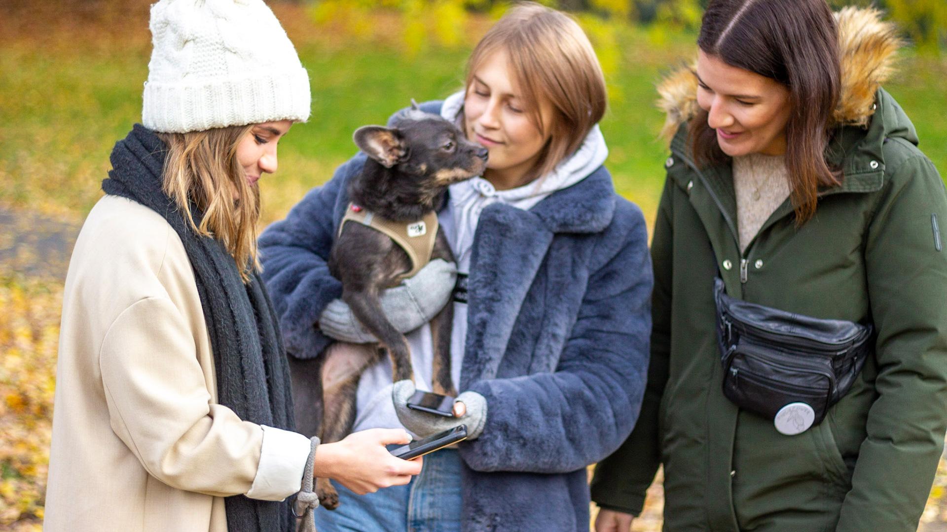 Drei Mädchen stehen draußen zusammen, eine trägt einen Hund auf dem Arm.