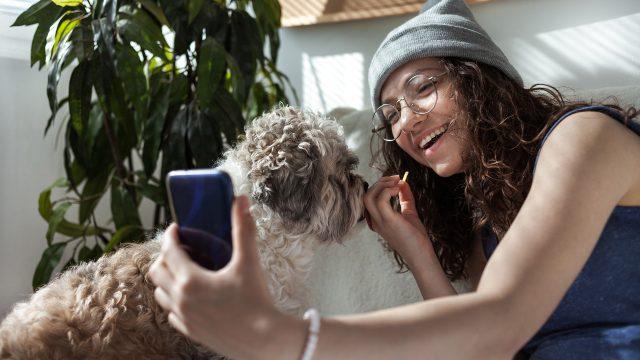 Eine Frau macht ein Foto von sich und ihrem Hund per Smartphone.