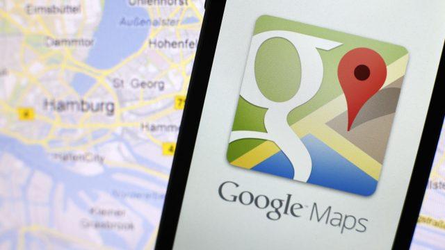 Google-Maps-App auf einem Smartphone neben einer Karte