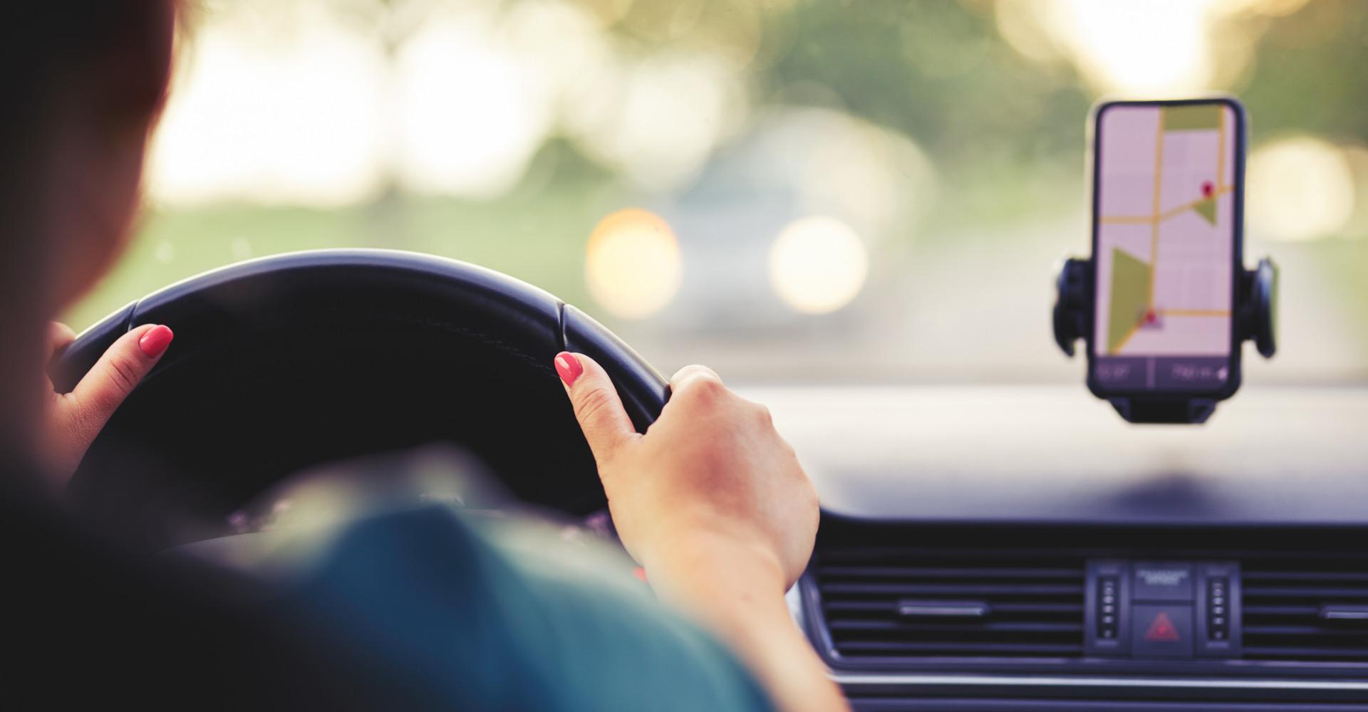 Frau fährt mit dem Auto, nutzt Google Maps auf dem Handy
