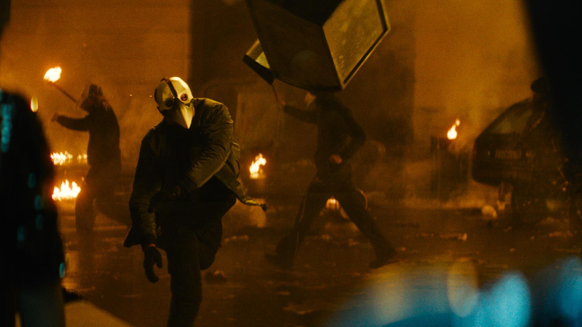 """Menschen mit einer Schnabelmaske randalieren im Film """"Major Grom: Der Pestdoktor"""" auf einer Straße."""