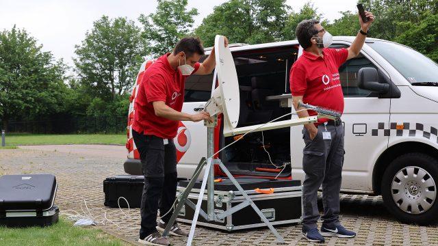 Zwei Techniker des Vodafone Instant Network Teams errichten eine Mini-Mobilfunkstation.