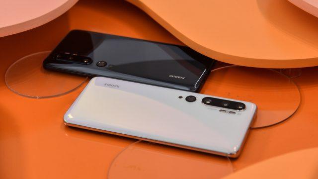 Zwei Xiaomi-Smartphones liegen auf orangefarbenem Untergrund