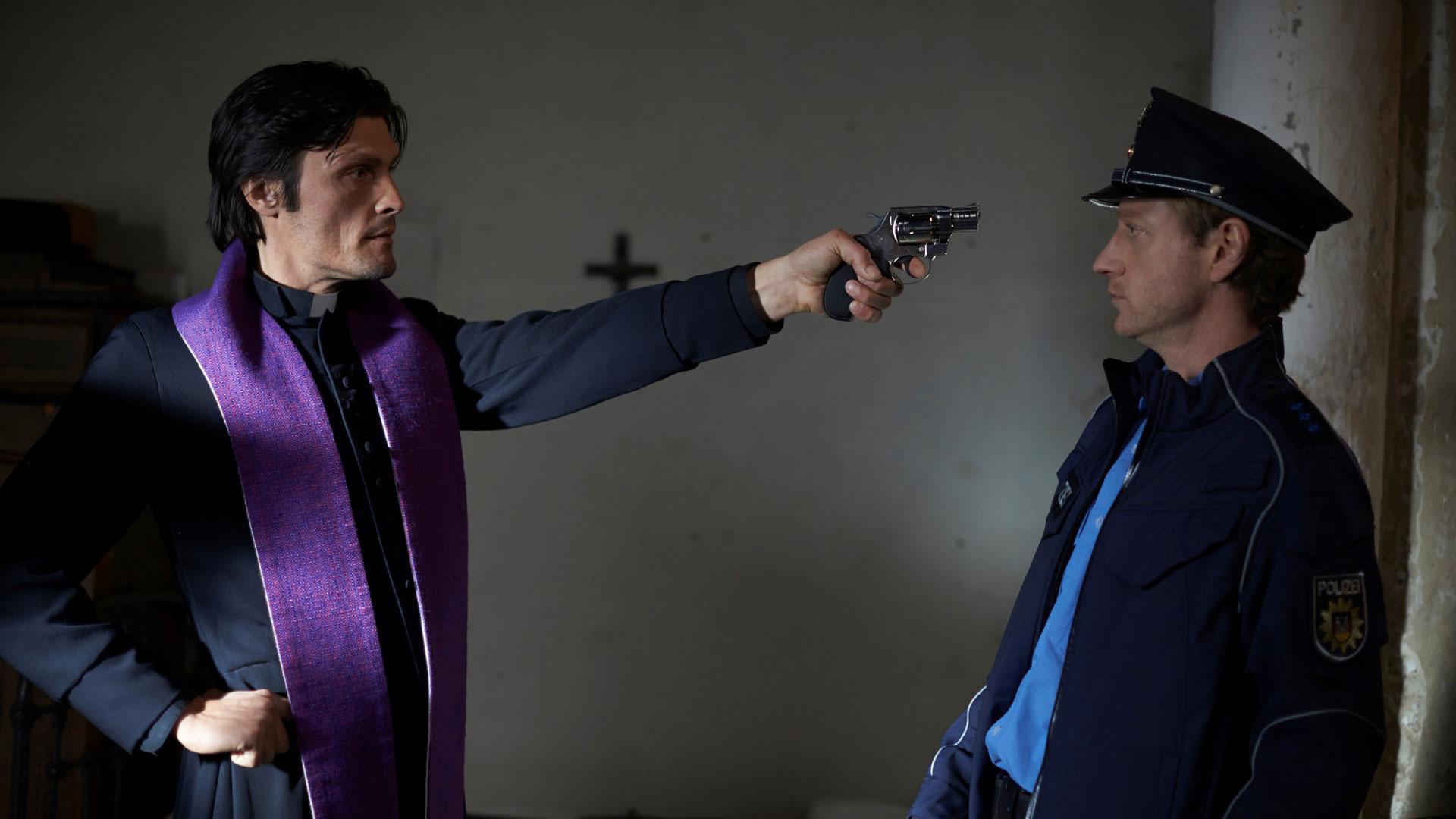 Ein Priester bedroht einen Polizisten mit einer Waffe