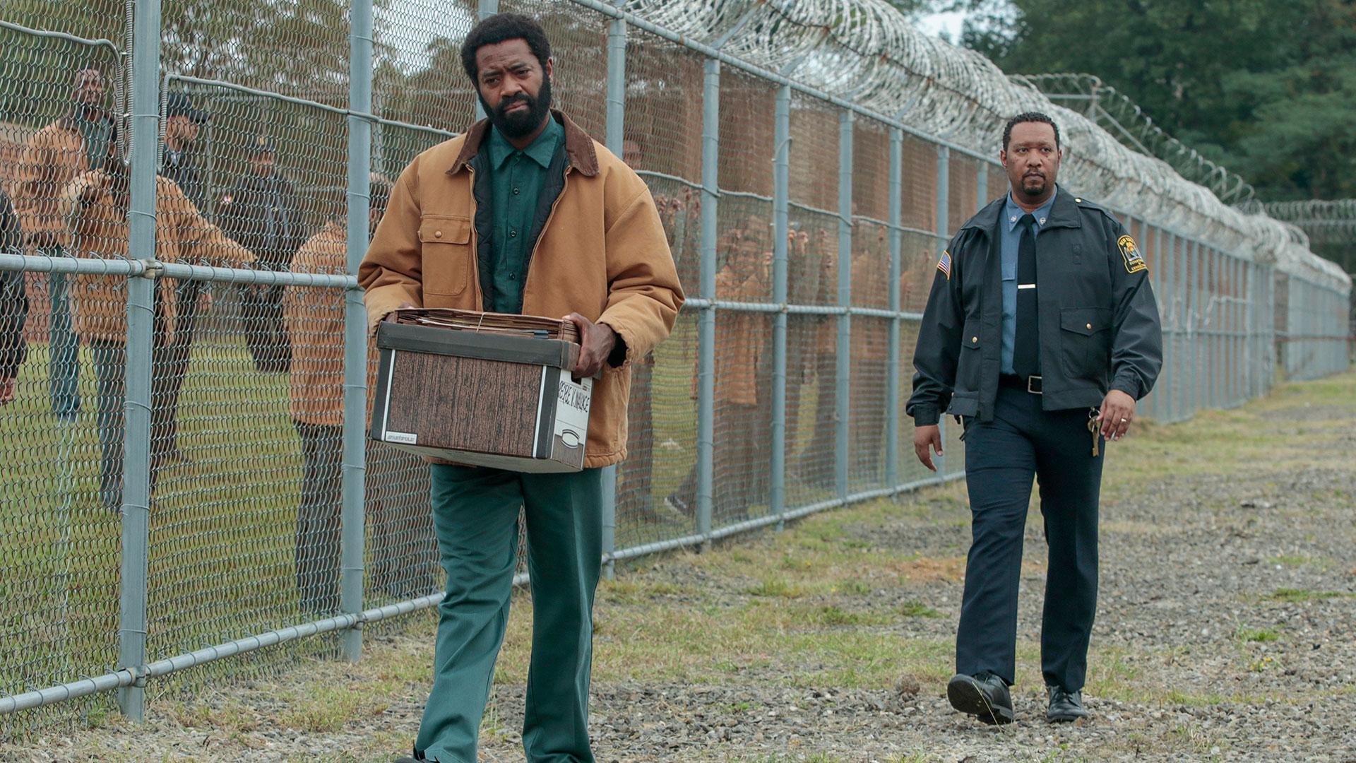 Ein Häftling läuft über den Hof eines Gefängnisses mit einem Karton voll Akten