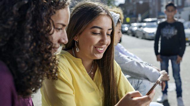 Zwei junge Frauen gucken draußen auf ein iPhone
