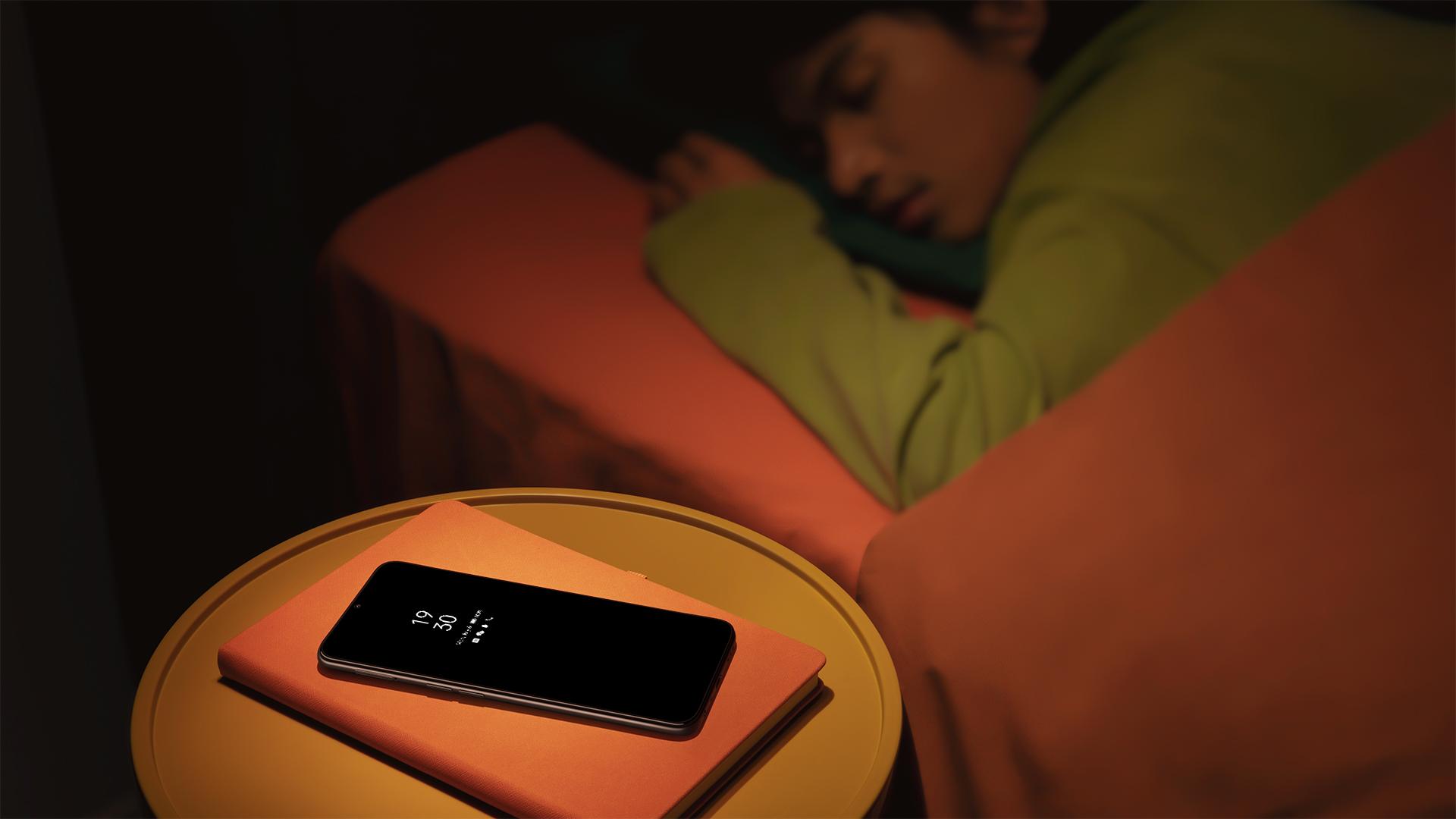 Ein Junge schläft, auf dem Nachttisch liegt ein Oppo A16s im Standby-Modus.
