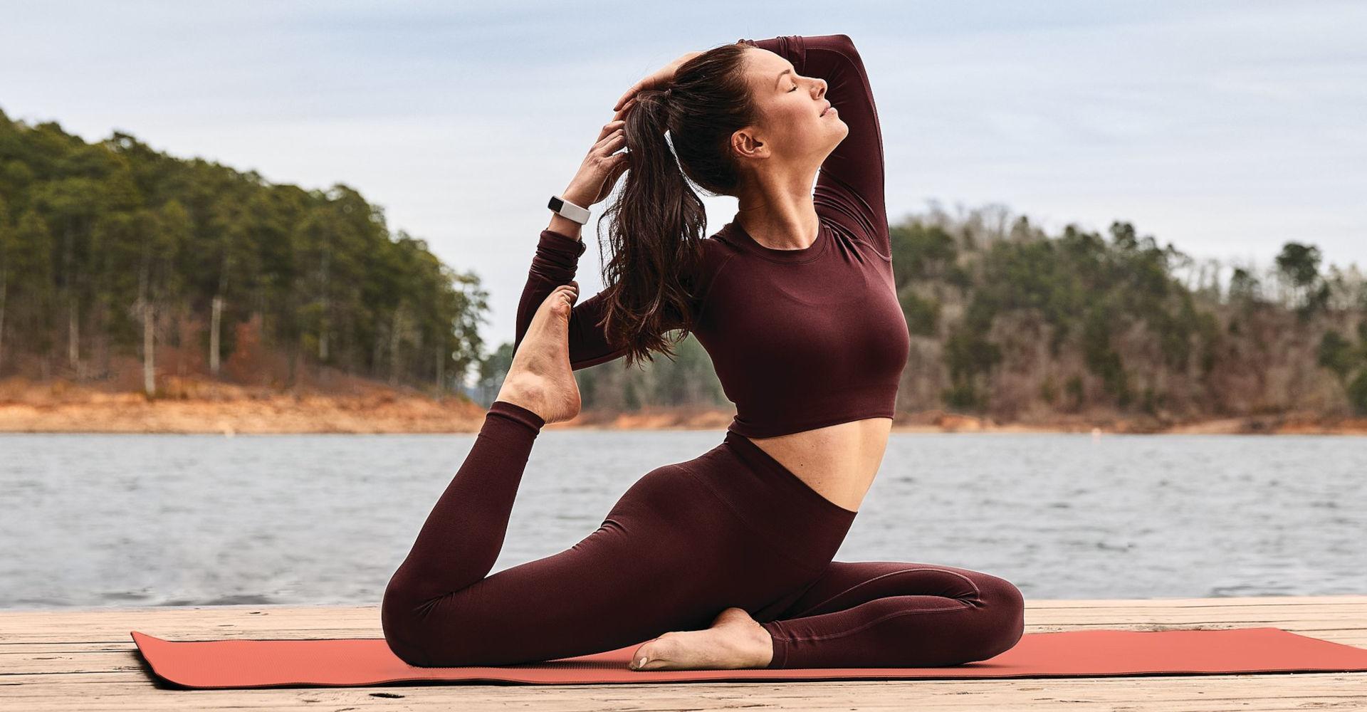 Eine Frau trägt die Fitbit Charge 5 beim Yoga