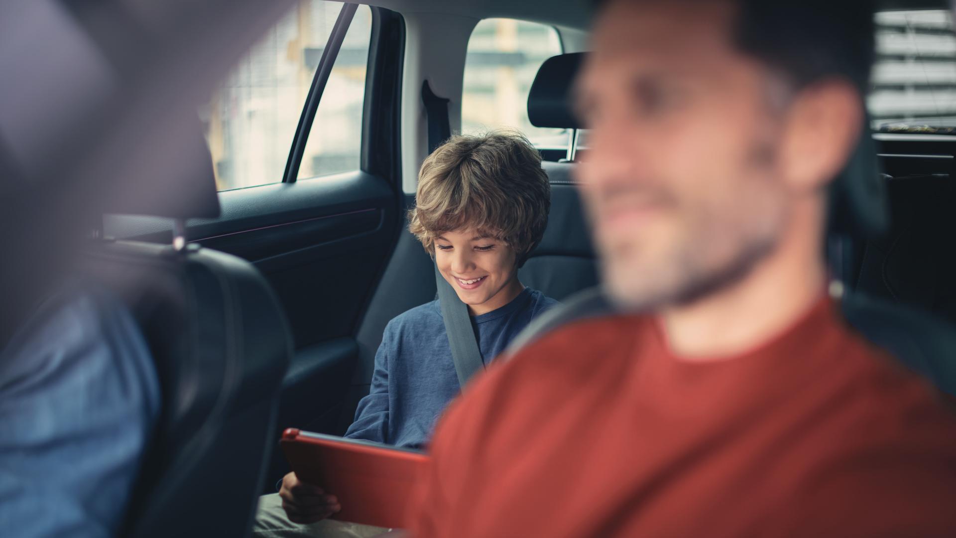 Eine Familie fährt im Auto, der Sohn sitzt auf dem Rücksitz liest etwas auf einem Tablet.