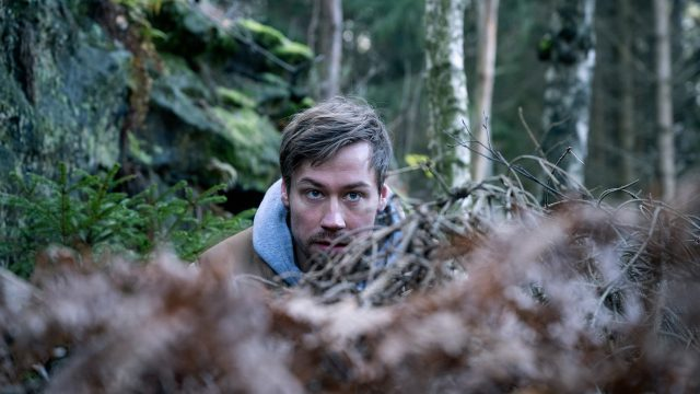 Roman (David Kross) versteckt sich im Wald hinter Ast-Gestrüpp.