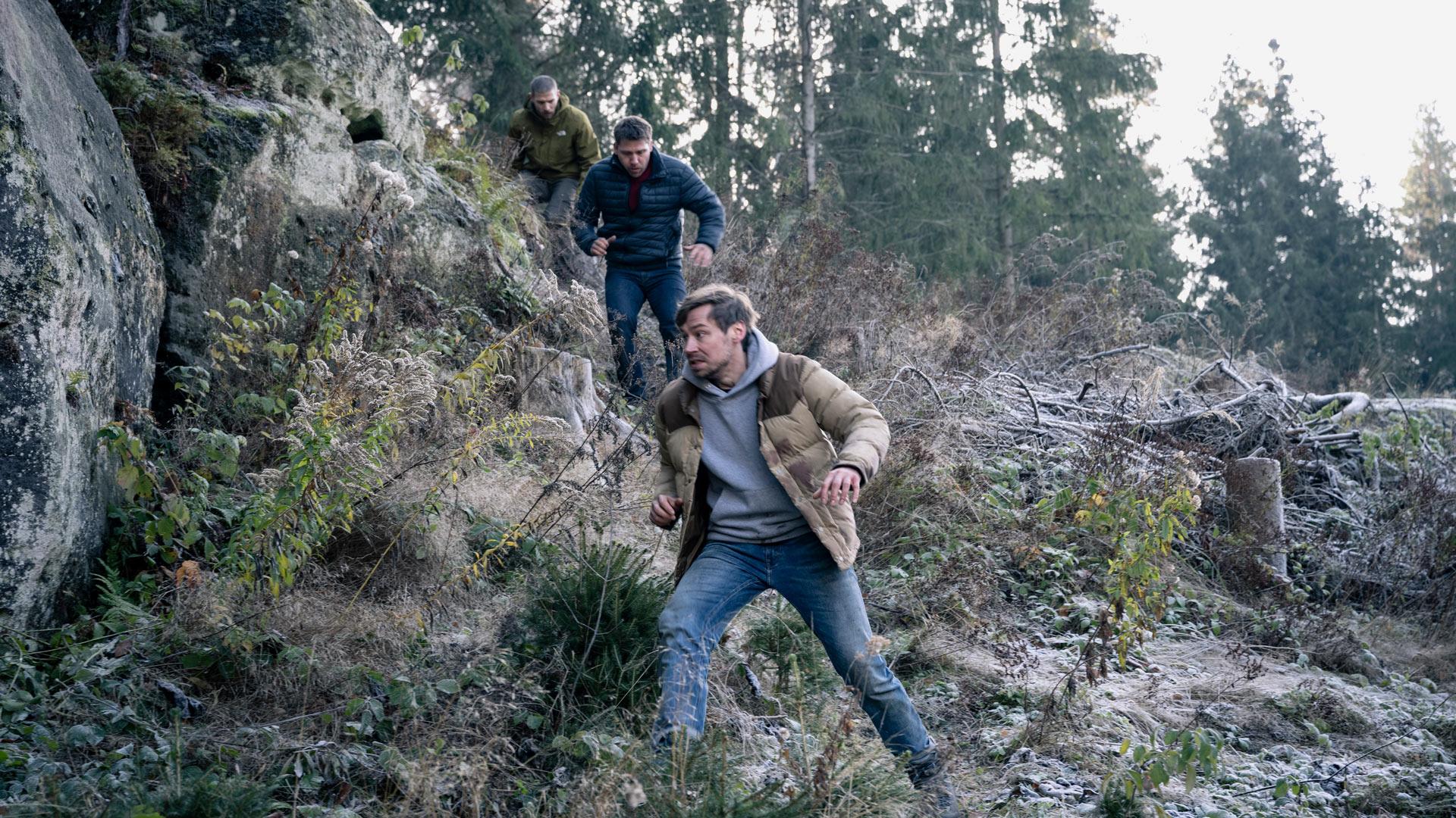 """Roman (David Kross), Albert (Hanno Koffler ) und Peter (Robert Finster) fliehen im Wald vor einem unbekannten Scharfschützen im Netflix-Thriller """"Prey""""."""
