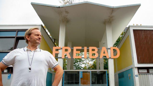 Bademeister Karl steht vor dem Freibad-Schild